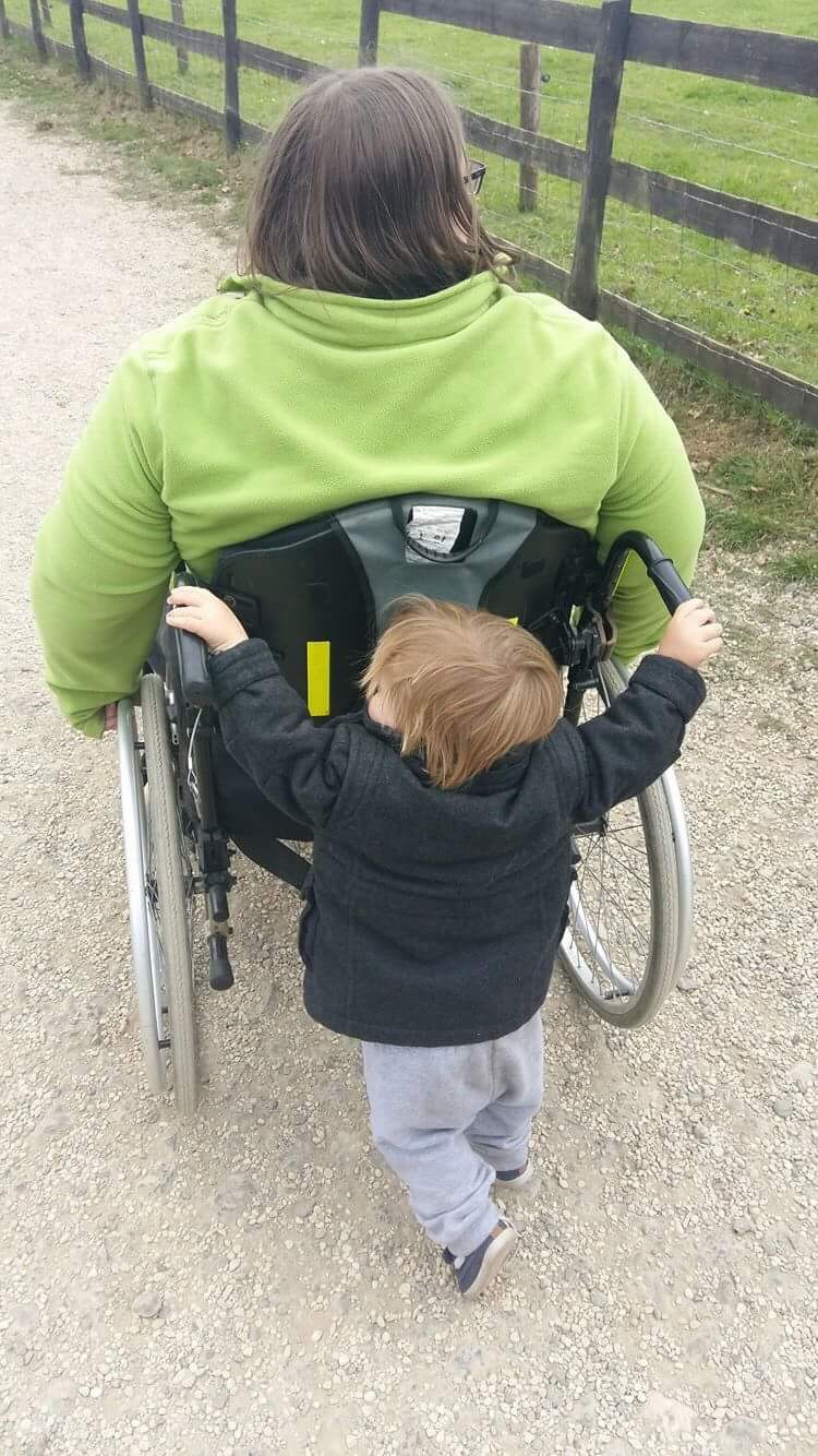 A blonde haired toddler having a go at pushing a woman in a green fleece in a manual wheelchair