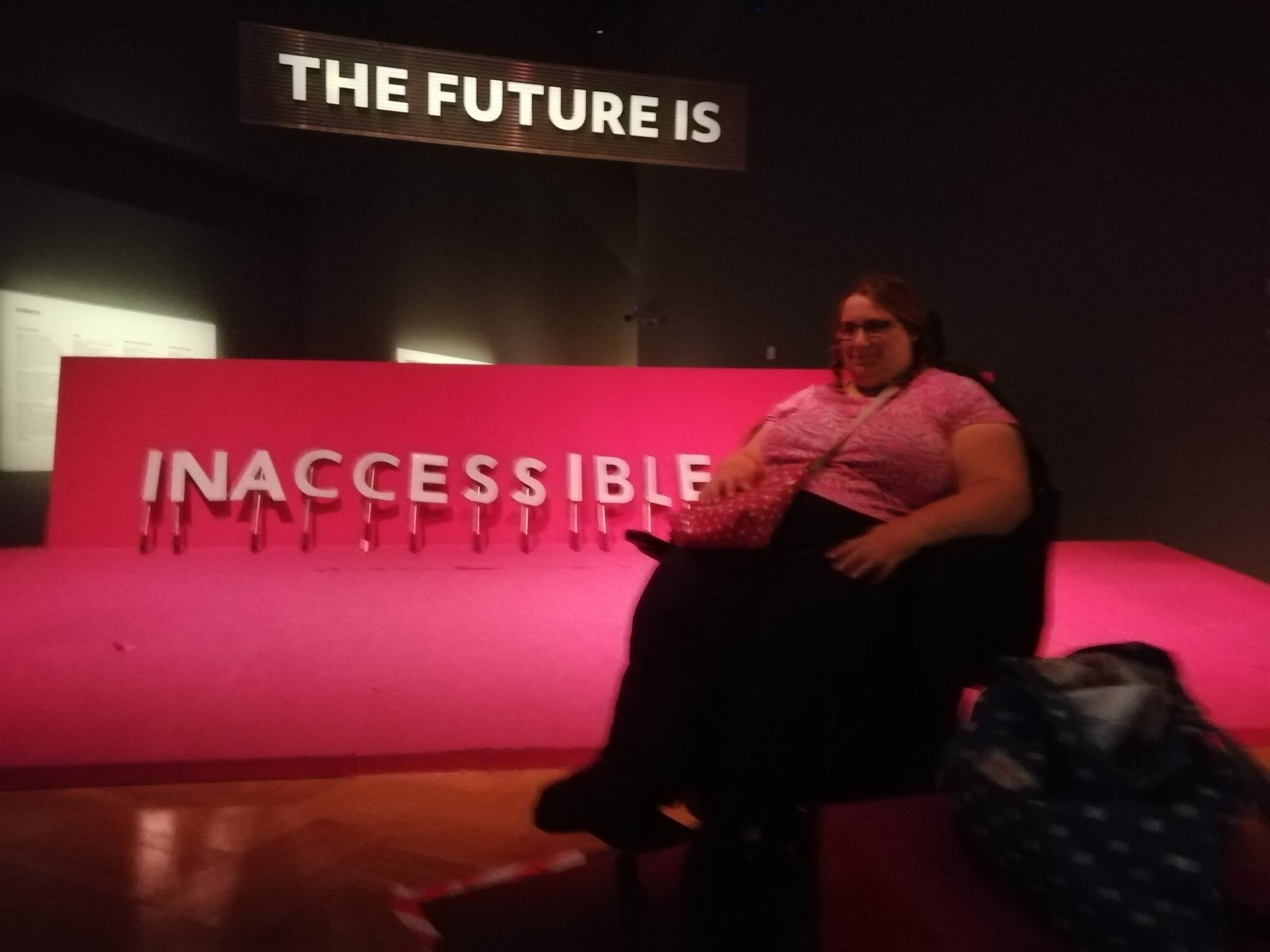 "Emma in her powerchair wearing a pink top with her hair in plaits. She's sitting in front of a bright pink stage that has a step to get on it. A sign above reads ""the future is"" and Emma's friend arranged letters on the stage to read ""inaccessible"""